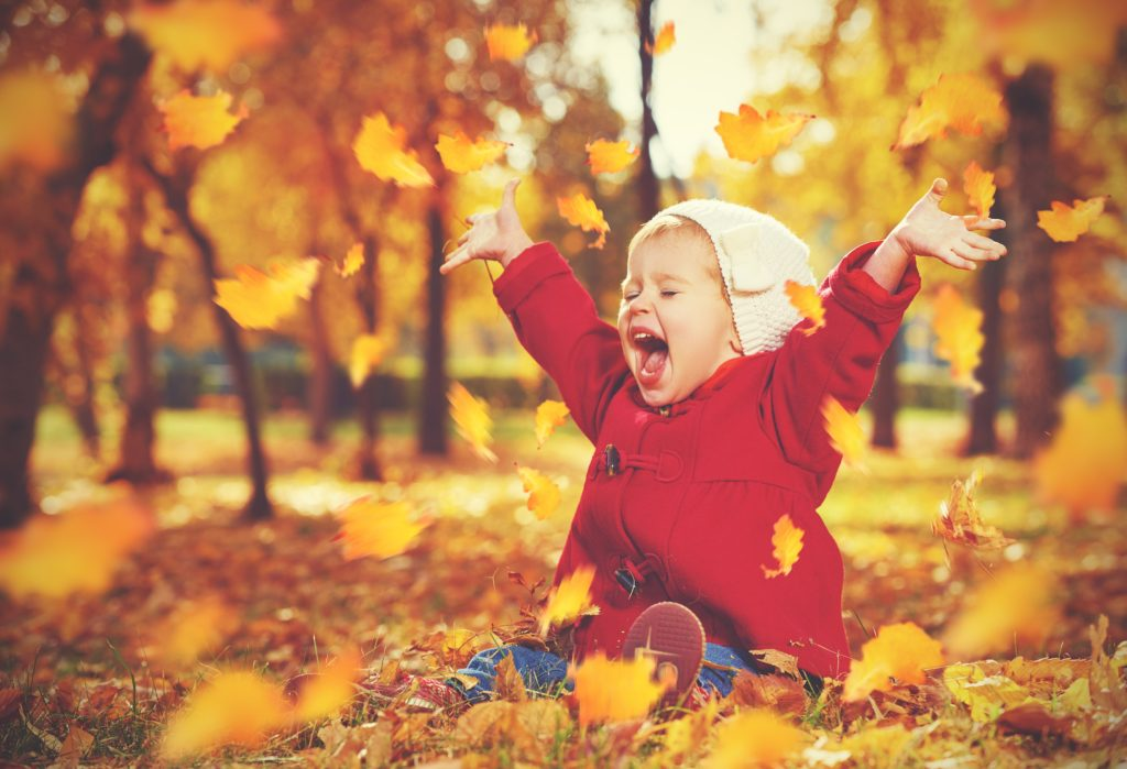 Little girl throwing leaves