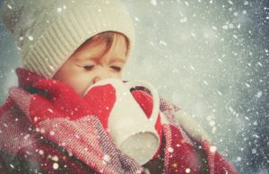 happy child girl with cup of hot drink on cold winter outdoors
